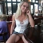 Slutty girl flashes her pussy in restaurant