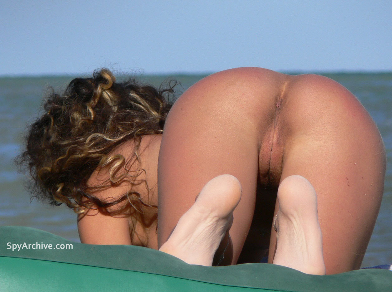 Spy shots of naked chick spreading at the beach - pussy view from public nude outdoor girl